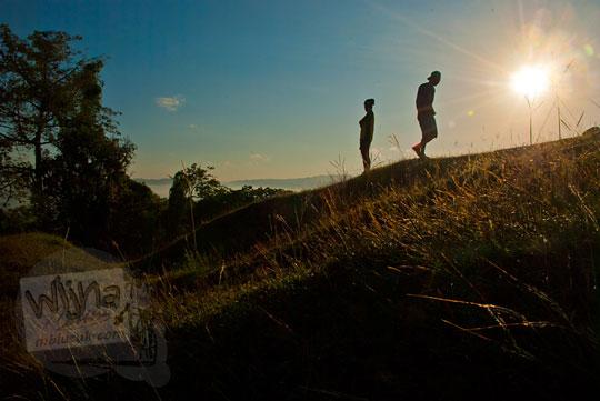 Foto siluet seorang pria berjalan mendaki bukit Candi Abang Jogotirto Berbah Sleman pada zaman dahulu Mei 2012