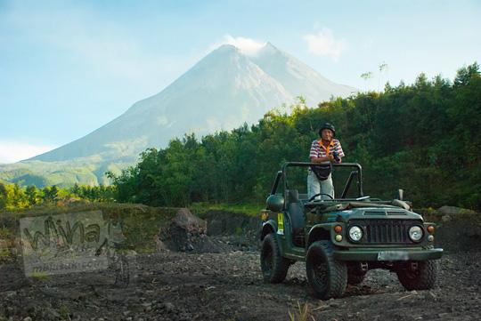 foto pria berpose di atas jeep wisata erupsi merapi pada zaman dulu september 2013