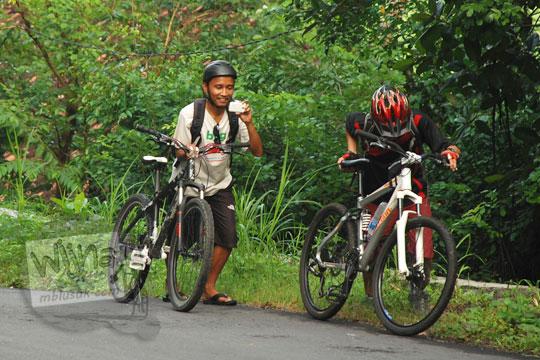 menuntun sepeda di tanjakan menuju curug kembar Prambanan di desa wisata Wukirharjo, Yogyakarta