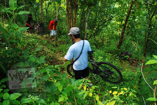 membawa sepeda mendekati lokasi curug kembar Prambanan di desa Wisata wukirharjo, Yogyakarta