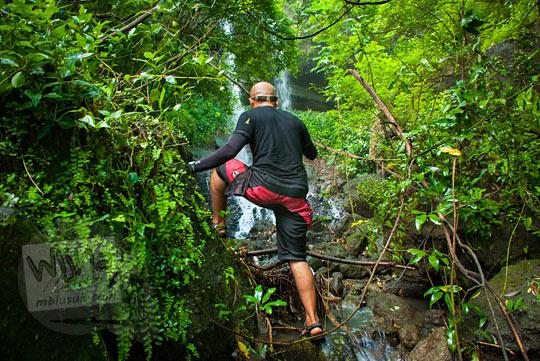 pria botak gundul mendaki tebing di curug kembar Prambanan di desa wisata Wukirharjo, Sleman