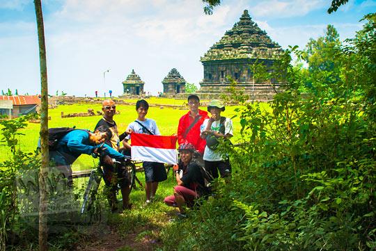 pesepeda berfoto bersama dengan bendera sangsaka merah putih berlatar candi ijo selepas berkunjung ke curug kembar Prambanan di desa Wukirharjo