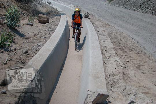 pesepeda bersepeda lewat saluran air demi menghindari debu vulkanik menuju Mata Air Bebeng di Glagaharjo, Cangkringan, Sleman