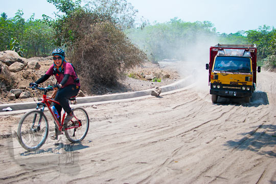 cewek berjilbab bersepeda melibas medan jalan berdebu vulkanik menuju Mata Air Bebeng di Glagaharjo