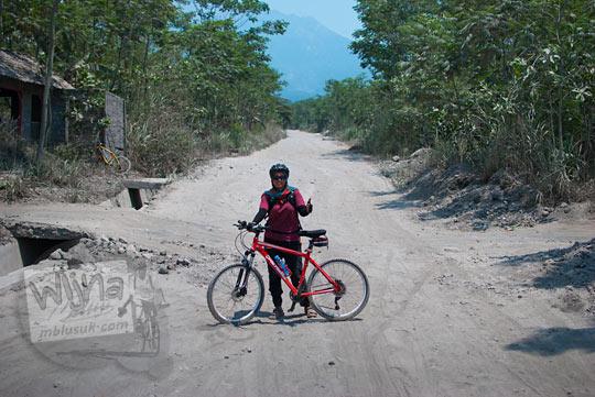 pesepeda cewek berjilbab berfoto dengan sepeda merah di gurun pasir cangkringan berlatar gunung merapi