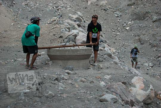 orang-orang berusaha mengangkat penutup sumur mata Air Bebeng di Glagaharjo