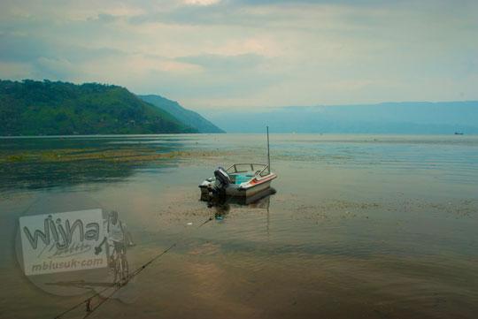 Sebuah kapal motor tampak rusak dan tidak terawat itu ditambatkan di lepas kotornya danau Toba di Kota Parapat, Sumatra Utara