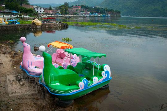 Dua buah perahu kayu berbentuk anjing laut teronggok di pinggir Danau Toba di kota Parapat, Sumatra Utara karena rusak dan sepi peminat
