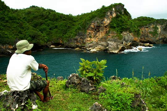 orang pacaran menikmati keindahan laut dari puncak bukit di kawasan Pantai Gesing, Gunungkidul