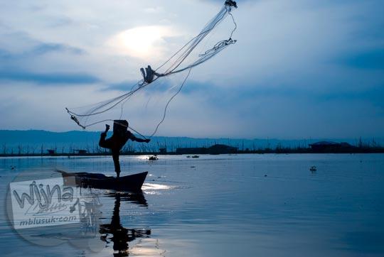 Seorang nelayan sedang melempar jaring ikan dari atas perahu di Rawa Pening di Ambarawa di tahun 2009