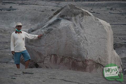 warga berpose dengan watu manten, batu besar di Kali Gendol yang terbawa awan panas erupsi Merapi tahun 2010