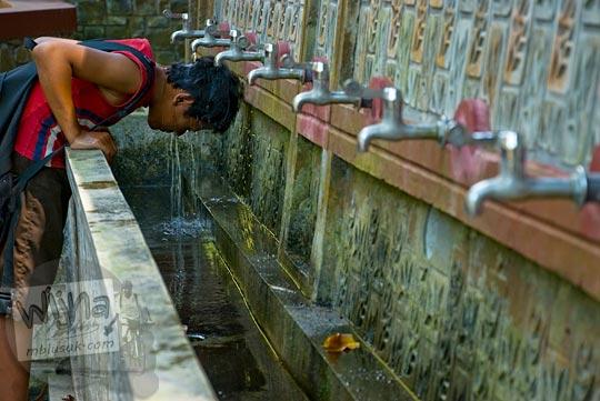 seorang anak kecil yang tinggal di sekitar kawasan ziarah Sendang Sono mengguyur kepalanya dengan air suci yang dialirkan lewat keran-keran yang berjumlah banyak
