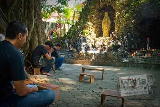 peziarah umat katolik berdoa hening di depan gua maria di dalam kawasan Sendangsono