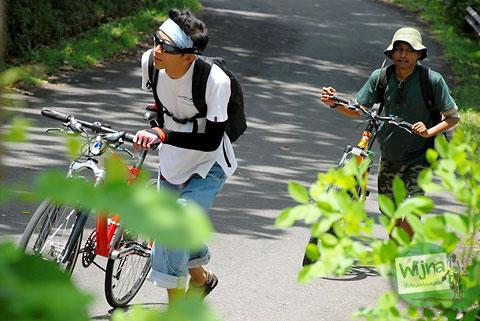 menuntun sepeda melewati tanjakan terjal menuju grojogan watu jonggol di desa nglinggo, Samigaluh, Yogyakarta