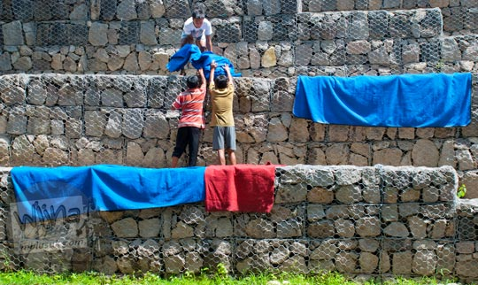 Foto warga menjemur karpet warna-warni di Umbul Cokro, Klaten di tahun 2009